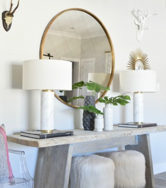 marble-and-brass-lamps-round-gold-mirror-fur-stools-rustic-modern-console-large-decorative-books-black-and-white-decor-ghost-chair-wall-antlers